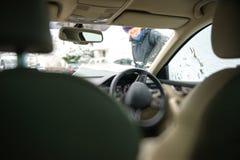 Κομψή γυναίκα επιχειρηματιών που καθαρίζει το δεξιά οδηγημένο ανεμοφράκτη αυτοκινήτων Στοκ εικόνα με δικαίωμα ελεύθερης χρήσης