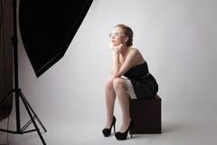 Κομψή γυναίκα κατά τη διάρκεια ενός πυροβολισμού φωτογραφιών Στοκ Φωτογραφίες