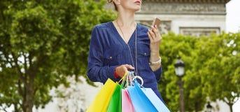 Κομψή γυναίκα με τις τσάντες αγορών που κρατά το smartphone, Παρίσι Στοκ Εικόνα