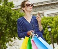Κομψή γυναίκα με τις τσάντες αγορών που κρατά το smartphone, Παρίσι Στοκ εικόνες με δικαίωμα ελεύθερης χρήσης