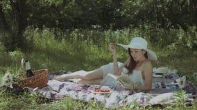 Κομψή γυναίκα που διαβάζει ένα βιβλίο στο θερινό πάρκο απόθεμα βίντεο