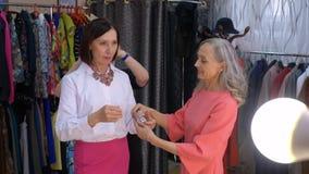 Κομψή γυναίκα που δοκιμάζει το περιδέραιο στην αίθουσα εκθέσεως εξαρτημάτων Πωλητής που βοηθά να δοκιμάσει το περιδέραιο μόδας στ απόθεμα βίντεο