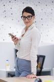 Κομψή γυναίκα που χρησιμοποιεί το κινητό τηλέφωνο στο κτίριο γραφείων ξεκινήματος Στοκ εικόνες με δικαίωμα ελεύθερης χρήσης