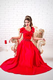 Κομψή γυναίκα σε μια μακροχρόνια κόκκινη συνεδρίαση φορεμάτων σε μια καρέκλα Στοκ Εικόνες