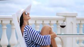 Κομψή γυναίκα στα γυαλιά ηλίου και καπέλο στη συνεδρίαση μπαλκονιών στην καρέκλα που αγκαλιάζει τα πόδια από τα διασχισμένα χέρια φιλμ μικρού μήκους