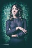 Κομψή γυναίκα στον εκλεκτής ποιότητας τοίχο με το πράσινο σχέδιο Στοκ Φωτογραφίες