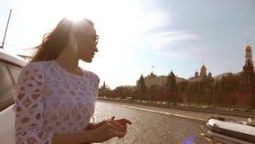 Κομψή γυναίκα στο άσπρο φόρεμα που εξετάζει τη Μόσχα Κρεμλίνο από μια βάρκα απόθεμα βίντεο