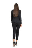 Κομψή γυναίκα στο επιχειρησιακό μαύρο κοστούμι που περπατά μακριά απομονωμένο οπισθοσκόπο λευκό Στοκ εικόνα με δικαίωμα ελεύθερης χρήσης