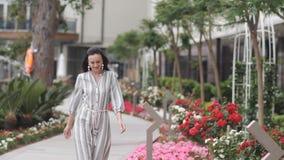 Κομψή γυναίκα στο μακρύ φόρεμα που περπατά μέσω του πάρκου πόλεων απόθεμα βίντεο