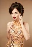 Κομψή γυναίκα στο χρυσό φόρεμα, κυρία μόδας στο ακριβό κρεμαστό κόσμημα j Στοκ φωτογραφία με δικαίωμα ελεύθερης χρήσης