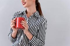 Κομψή επιχειρηματίας που πίνει το καυτό ποτό Στοκ εικόνα με δικαίωμα ελεύθερης χρήσης