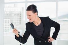 Κομψή επιχειρηματίας που φωνάζει στο τηλέφωνο Στοκ Φωτογραφία
