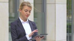Κομψή επιχειρησιακή γυναίκα με τον υπολογιστή ταμπλετών κοντά στο κτίριο γραφείων κλείστε επάνω φιλμ μικρού μήκους