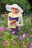 Κομψή ηλικιωμένη γυναικεία ανάγνωση στον κήπο της Στοκ εικόνες με δικαίωμα ελεύθερης χρήσης