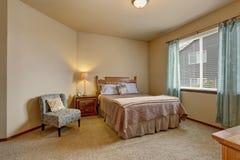 Κομψή κρεβατοκάμαρα στα μαλακά χρώματα με τις μπλε κουρτίνες και το μπεζ κρεβάτι στοκ φωτογραφίες