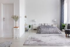 Κομψή κρεβατοκάμαρα ύφους της Νέας Υόρκης με το άνετο κρεβάτι, πραγματική φωτογραφία με το διάστημα αντιγράφων στον άσπρο τοίχο στοκ εικόνες με δικαίωμα ελεύθερης χρήσης