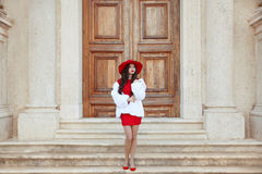κομψή κυρία Γυναίκα μόδας στο κόκκινο καπέλο και φόρεμα που φορά στο μόριο Στοκ Φωτογραφίες