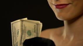 Κομψή κυρία που παρουσιάζει δέσμη των δολαρίων στη κάμερα που απομονώνεται στο μαύρο υπόβαθρο απόθεμα βίντεο