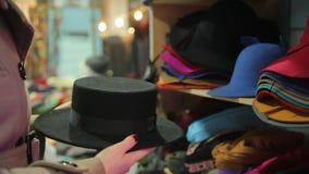 Κομψή κυρία που ψάχνει το κατάλληλο καπέλο στο τμήμα εξαρτημάτων, εμπορικό κέντρο απόθεμα βίντεο