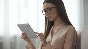 Κομψή κυρία στα γυαλιά που αναλύουν τις επιστολές ηλεκτρονικού ταχυδρομείου, που ελέγχουν inbox το φάκελλο στην ταμπλέτα φιλμ μικρού μήκους