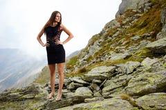 Κομψή κυρία στο φόρεμα που στέκεται στους βράχους βουνών Στοκ Εικόνες