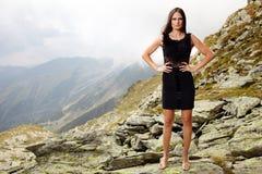 Κομψή κυρία στο φόρεμα που στέκεται στους βράχους βουνών Στοκ Εικόνα