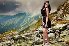 Κομψή κυρία στο φόρεμα που στέκεται στους βράχους βουνών Στοκ Φωτογραφία