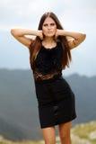 Κομψή κυρία στο φόρεμα που στέκεται στους βράχους βουνών Στοκ εικόνες με δικαίωμα ελεύθερης χρήσης