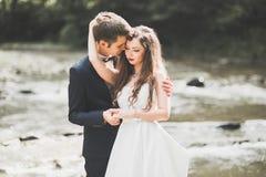 Κομψή μοντέρνη ευτυχής νύφη brunette και πανέμορφος νεόνυμφος στο υπόβαθρο ενός όμορφου ποταμού στα βουνά στοκ εικόνα με δικαίωμα ελεύθερης χρήσης