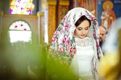 Κομψή μοντέρνη νύφη με το floral μαντίλι για το κεφάλι στην παλαιά εκκλησία, weddin Στοκ Φωτογραφία