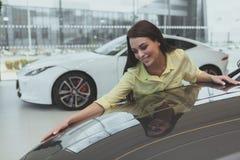 Κομψή νέα γυναίκα που αγοράζει το νέο αυτοκίνητο στον αντιπρόσωπο στοκ εικόνες