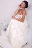 Κομψή νύφη στην τοποθέτηση γαμήλιων φορεμάτων στο διακοσμημένο στούντιο Στοκ Εικόνες