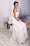 Κομψή νύφη στη συνεδρίαση γαμήλιων φορεμάτων στην ταλάντευση στο στούντιο Στοκ Φωτογραφίες
