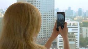 Κομψή ξανθή γυναίκα που κάνει μια φωτογραφία στο τηλέφωνο η γυναίκα φωτογραφίζει την άποψη από το παράθυρο των ουρανοξυστών στοκ εικόνες