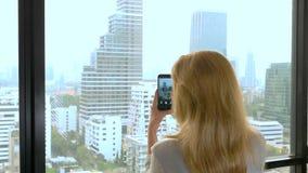 Κομψή ξανθή γυναίκα που κάνει μια φωτογραφία στο τηλέφωνο η γυναίκα φωτογραφίζει την άποψη από το παράθυρο των ουρανοξυστών στοκ φωτογραφία