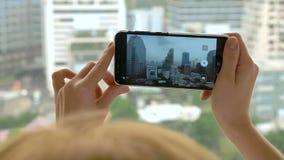 Κομψή ξανθή γυναίκα που κάνει μια φωτογραφία στο τηλέφωνο η γυναίκα φωτογραφίζει την άποψη από το παράθυρο των ουρανοξυστών στοκ φωτογραφίες με δικαίωμα ελεύθερης χρήσης