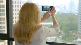Κομψή ξανθή γυναίκα που κάνει μια φωτογραφία στο τηλέφωνο η γυναίκα φωτογραφίζει την άποψη από το παράθυρο των ουρανοξυστών στοκ φωτογραφία με δικαίωμα ελεύθερης χρήσης
