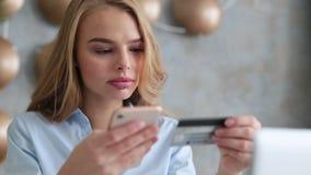 Κομψή ξανθή συνεδρίαση γυναικών στο γραφείο που κρατούν το κινητό τηλέφωνο και την πλαστική κάρτα υπογράφοντας επάνω στον ιστοχώρ απόθεμα βίντεο