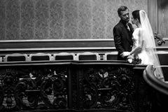 Κομψή πανέμορφη νύφη και μοντέρνη τοποθέτηση νεόνυμφων στον παλαιό τοίχο μέσα Στοκ φωτογραφία με δικαίωμα ελεύθερης χρήσης