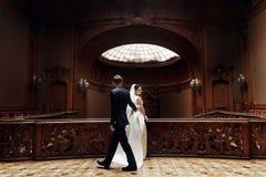Κομψή πανέμορφη νύφη και μοντέρνη τοποθέτηση νεόνυμφων στο παλαιό ξύλινο ST Στοκ Εικόνες