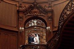Κομψή πανέμορφη νύφη και μοντέρνος νεόνυμφος που στέκονται στο ξύλινο stai Στοκ Εικόνα