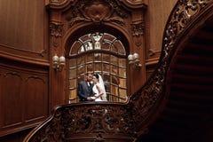 Κομψή πανέμορφη νύφη και μοντέρνος νεόνυμφος που στέκονται στο ξύλινο stai Στοκ Φωτογραφία