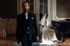 Κομψή πανέμορφη νύφη που παίζει το fortepiano και το μοντέρνο handso Στοκ φωτογραφία με δικαίωμα ελεύθερης χρήσης