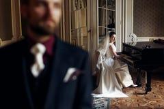 Κομψή πανέμορφη νύφη που παίζει το fortepiano και το μοντέρνο handso Στοκ Φωτογραφία