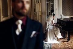 Κομψή πανέμορφη νύφη που παίζει το fortepiano και το μοντέρνο handso Στοκ Εικόνες