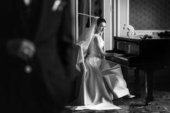 Κομψή πανέμορφη νύφη που παίζει το fortepiano στην πλούσια παλαιά αίθουσα α Στοκ εικόνες με δικαίωμα ελεύθερης χρήσης