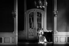 Κομψή πανέμορφη νύφη που παίζει το fortepiano στο πλούσιο παλαιό δωμάτιο Στοκ Φωτογραφία