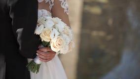Κομψή τοποθέτηση νυφών και νεόνυμφων μαζί υπαίθρια σε μια ημέρα γάμου Νύφη που κρατά μια άσπρη ροδαλή ανθοδέσμη στεμένος στοκ φωτογραφίες με δικαίωμα ελεύθερης χρήσης