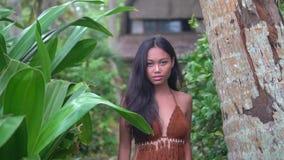 Κομψή τοποθέτηση brunette ενάντια στο σκηνικό της καλύβας στις ζούγκλες, που πηγαίνει προς τη κάμερα απόθεμα βίντεο