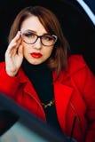 Κομψή όμορφη γυναίκα με τα γυαλιά για το όραμα που εξετάζει τη κάμερα Φωτεινό makeup, κόκκινα χείλια, κόκκινο κραγιόν κυρία Στοκ Φωτογραφίες